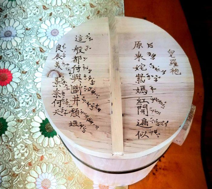 Woodburned art. Kunqu music from The Peony Pavilion on wooden rice bucket. 熱烙工藝。牡丹亭昆曲譜烙在木飯桶上。